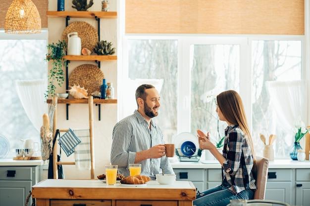 Glimlachend mooi stel dat overdag in de keuken zit en praat tijdens hun maaltijd