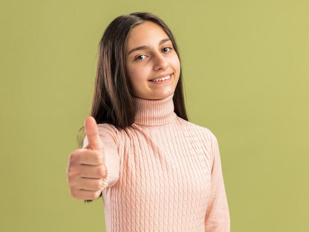 Glimlachend mooi tienermeisje dat naar de voorkant kijkt en duim omhoog houdt geïsoleerd op olijfgroene muur green