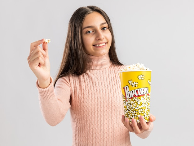 Glimlachend mooi tienermeisje dat naar de voorkant kijkt en een emmer popcorn en popcornstuk uitrekt naar camera geïsoleerd op een witte muur