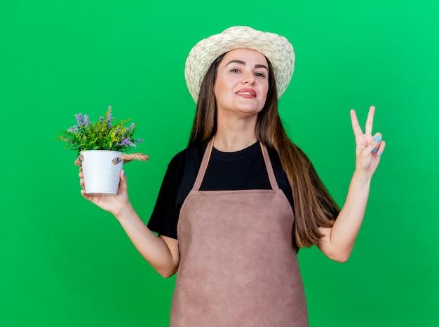 Glimlachend mooi tuinman meisje in uniform dragen tuinieren hoed bedrijf bloem in bloempot weergegeven: vredesgebaar geïsoleerd op groene achtergrond
