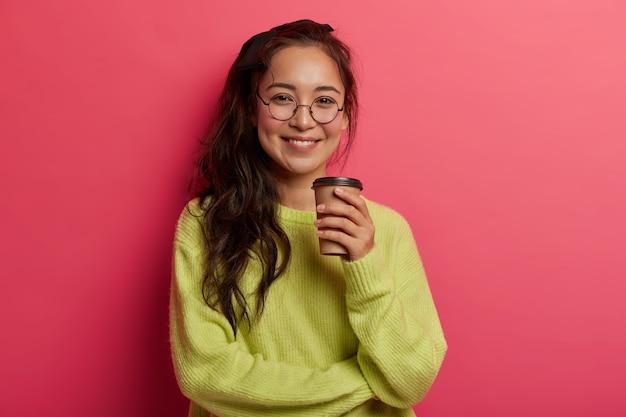 Glimlachend mooi vrouwelijk model geniet van het drinken van koffie in de vrije tijd, heeft een goed humeur, informeel gesprek met intelocutor, kijkt direct naar de camera