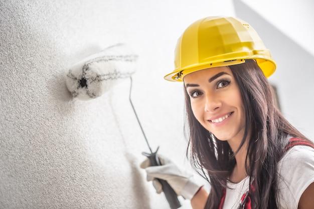 Glimlachend mooi vrouwtje met een helm die de muur schildert met een roller.