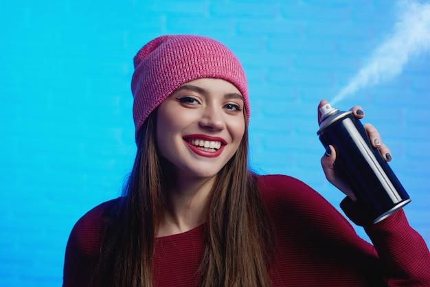 Glimlachend mooi wijfje met lang haar die rode hoed en sweater het stellen met verfnevel dragen in haar handen