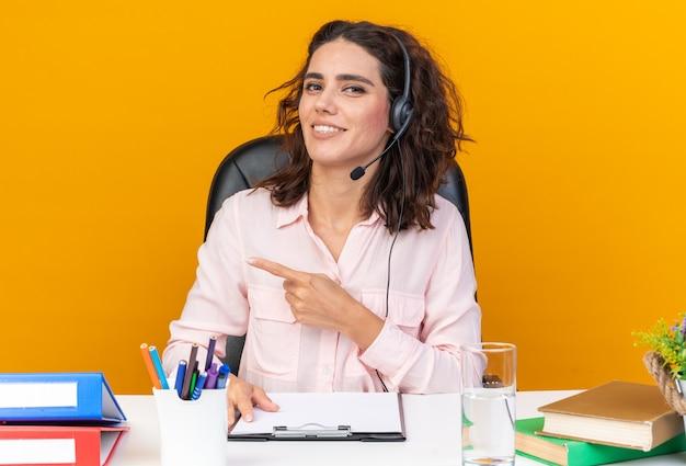 Glimlachend mooie blanke vrouwelijke callcenter-operator op koptelefoon zittend aan bureau met kantoorhulpmiddelen wijzend naar kant geïsoleerd op oranje muur