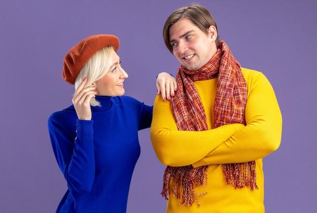 Glimlachend mooie blonde vrouw met baret kijken naar knappe slavische man met sjaal om zijn nek staande met gekruiste armen geïsoleerd op paarse muur met kopie ruimte