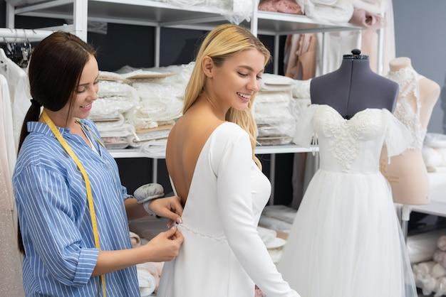 Glimlachend mooie bruid passende witte backless trouwjurk terwijl kleermaker haar bijstaat in de studio