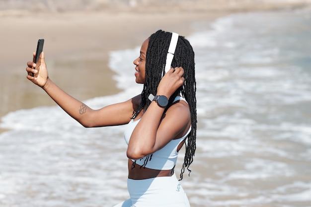 Glimlachend mooie fit jonge vrouw selfie te nemen op het strand na het joggen in de ochtend