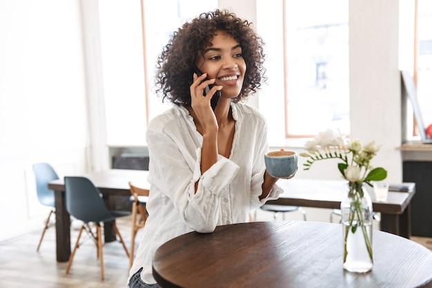 Glimlachend mooie jonge afrikaanse vrouw binnenshuis ontspannen, met behulp van mobiele telefoon, praten