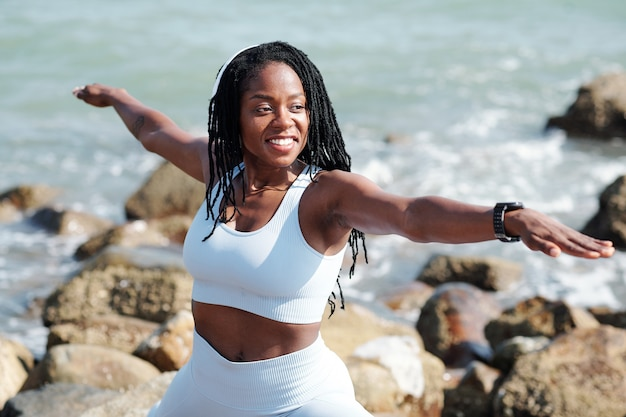 Glimlachend mooie jonge fit sportvrouw beoefenen krijger pose op rotsachtig strand