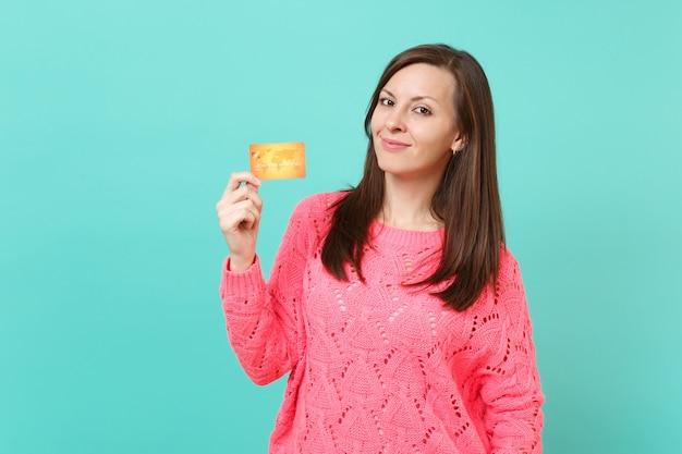 Glimlachend mooie jonge vrouw in gebreide roze trui op zoek naar camera, creditcard in de hand houden geïsoleerd op blauwe turquoise muur achtergrond studio portret. mensen levensstijl concept. bespotten kopie ruimte.