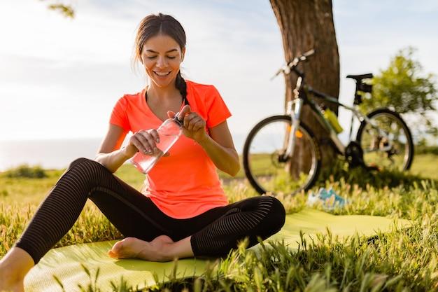 Glimlachend mooie vrouw drinkwater in fles sporten in de ochtend in park