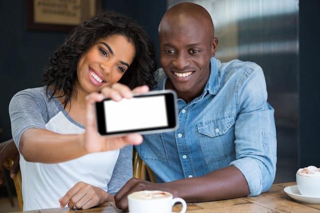 Glimlachend multi-etnisch paar dat selfie met slimme telefoon in coffeeshop neemt