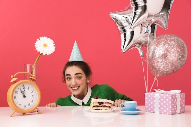 Glimlachend mysterie jong nerd student meisje viert haar verjaardag en verstopt zich achter de tafel tijdens het kijken