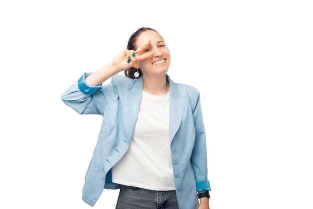 Glimlachend naar de camera maakt de vrouw het v-gebaar voor haar oog.