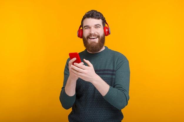 Glimlachend naar de cameraman houdt een telefoon en luistert naar de muziek via een headset.