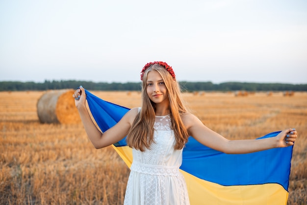 Glimlachend oekraïens meisje dat in witte kleding en rode haarhoepel blauwe en gele vlag houdt