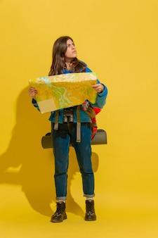 Glimlachend, op zoek naar een manier. portret van een vrolijk jong kaukasisch toeristenmeisje met zak en verrekijker dat op gele studioachtergrond wordt geïsoleerd. voorbereiden op reizen. resort, menselijke emoties, vakantie.