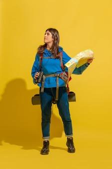 Glimlachend, op zoek naar een manier. portret van een vrolijk jong kaukasisch toeristenmeisje met zak en verrekijker dat op gele studioachtergrond wordt geïsoleerd.
