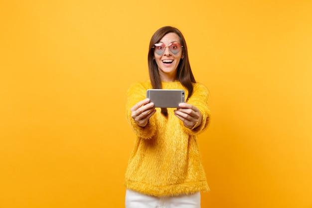 Glimlachend opgewonden jonge vrouw in bont trui, hart bril doen selfie schot op mobiele telefoon geïsoleerd op heldere gele achtergrond. mensen oprechte emoties, lifestyle concept. reclame gebied.