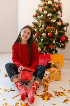 Glimlachend opgewonden mooie vrouw in rode trui om thuis te zitten bij de kerstboom uitpakken van cadeautjes en geschenkdozen