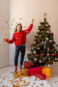 Glimlachend opgewonden mooie vrouw in rode trui om thuis te zitten op kerstboom gouden confetti omgeven met cadeautjes en geschenkdozen gooien