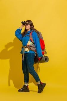 Glimlachend, opkijkend. portret van een vrolijk jong kaukasisch toeristenmeisje met zak en verrekijker dat op gele studioachtergrond wordt geïsoleerd. voorbereiden op reizen. resort, menselijke emoties, vakantie.