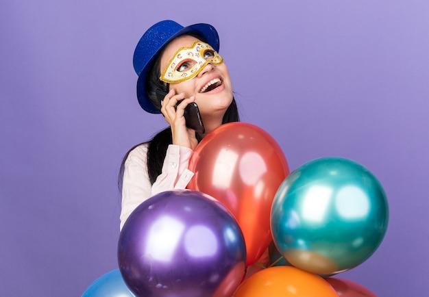 Glimlachend opzoeken van jong mooi meisje met feestmuts en maskerade oogmasker staande achter ballonnen spreekt op telefoon geïsoleerd op blauwe muur