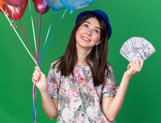 Glimlachend opzoeken van jong mooi meisje met feestmuts met ballonnen met contant geld