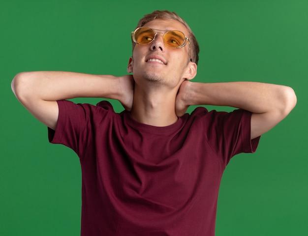 Glimlachend opzoeken van jonge knappe kerel met een rood shirt en een bril die handen op de nek legt die op een groene muur is geïsoleerd