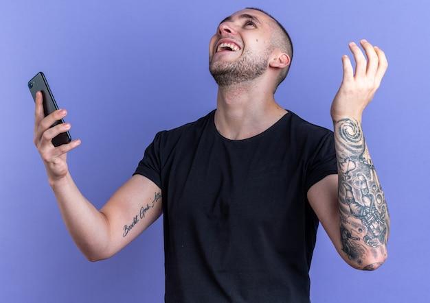 Glimlachend opzoeken van jonge knappe kerel met een zwart t-shirt met telefoon geïsoleerd op een blauwe muur