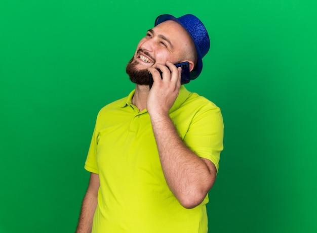 Glimlachend opzoeken van jonge man met blauwe feestmuts spreekt op telefoon geïsoleerd op groene muur