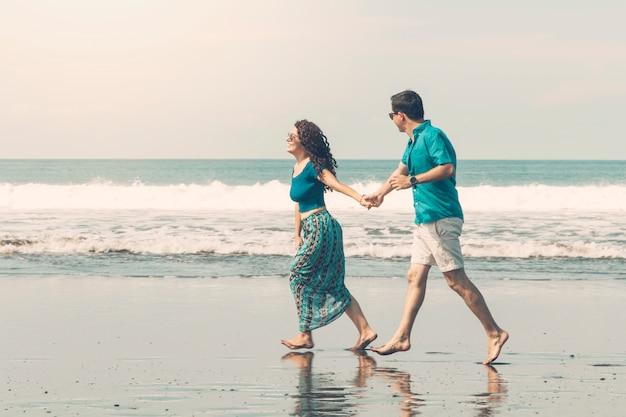 Glimlachend paar blootvoets wandelen langs het strand