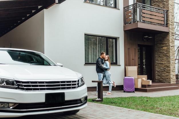 Glimlachend paar dat dichtbij hun moderne villa koestert. bewegende tijd.