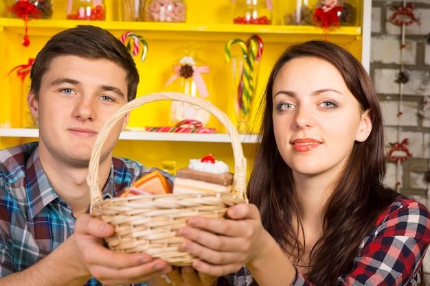 Glimlachend paar dat een rieten mand met replicakoekjes en -cakes omhoog houdt met een kleurrijk geel welsh dressoir met glazen potten en snoeprietjes op de achtergrond