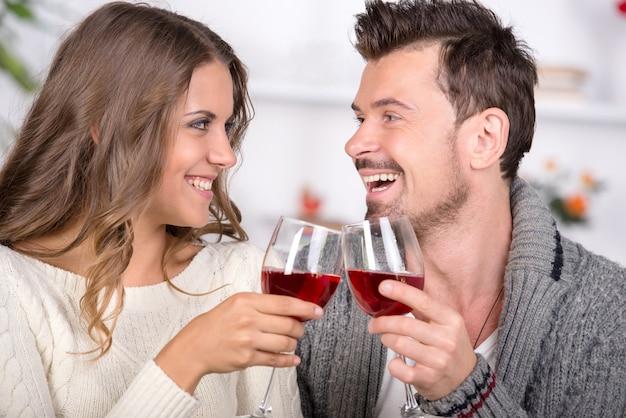 Glimlachend paar dat en rode wijn thuis dateert drinkt.