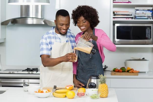 Glimlachend paar dat fruit smoothie in keuken voorbereidt