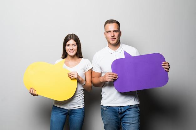 Glimlachend paar dat gele en blauwe praatjewolken in hun handen houdt die op witte achtergrond worden geïsoleerd