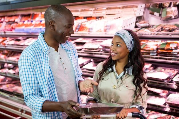 Glimlachend paar dat in kruidenierswinkelsectie winkelt
