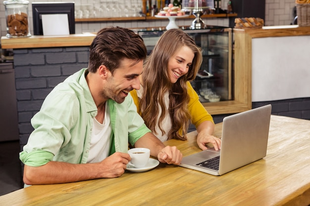 Glimlachend paar dat laptop met behulp van