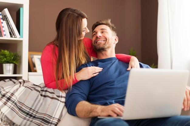 Glimlachend paar dat laptop thuis met behulp van