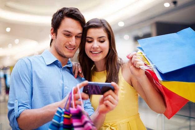 Glimlachend paar dat mobiele telefoon bekijkt