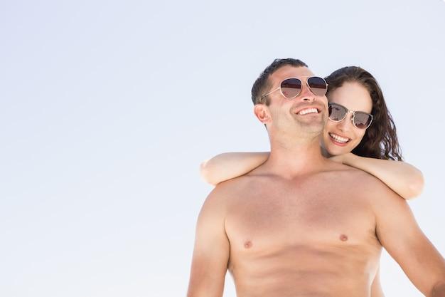 Glimlachend paar dat op het strand koestert