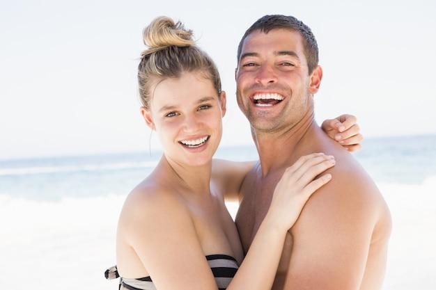 Glimlachend paar dat op het strand omhelst