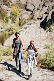 Glimlachend paar dat samen met rugzakken over bergen loopt