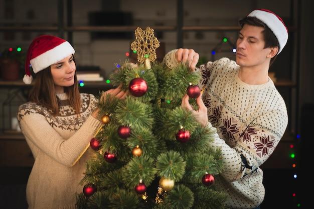 Glimlachend paar die kerstmisboom met bollen verfraaien