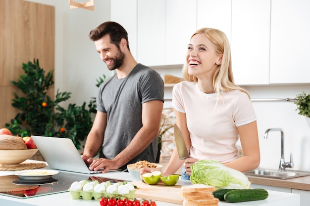 Glimlachend paar die notitieboekje gebruiken om in hun keuken te koken