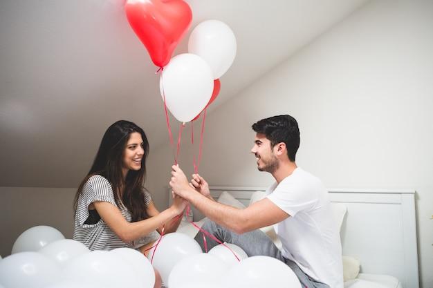 Glimlachend paar die rode en witte ballonnen