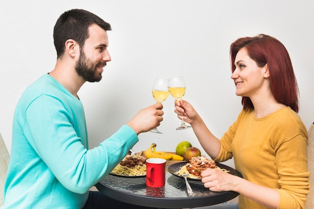Glimlachend paar die van drank met voedsel thuis genieten