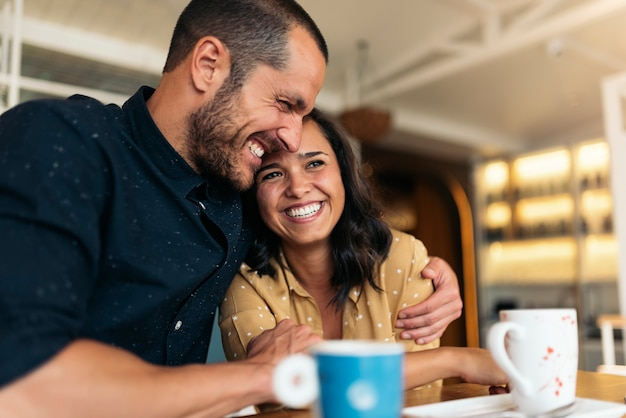 Glimlachend paar geliefden die plezier hebben in de coffeeshop.