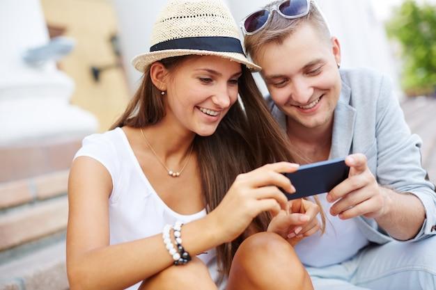 Glimlachend paar het lezen van sms-berichten